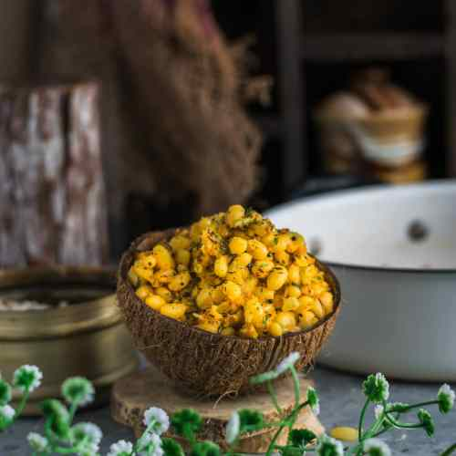 an empty coconut shell filled with navy beans sundal