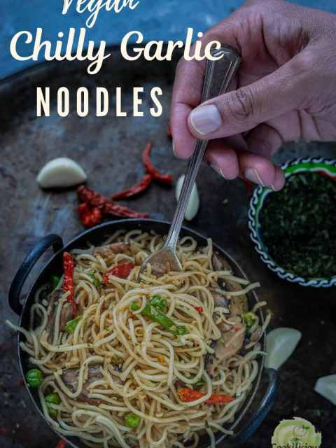 close up shot of a hand digging a fork into a bowl of Chilly Garlic Noodles with text at the top