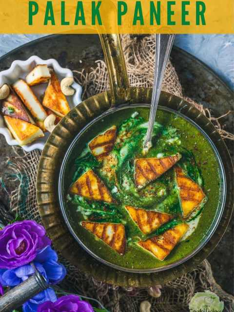 Restaurant Style Palak Paneer in a round platter with a spoon in it and some grilled paneer on the side and text at the top