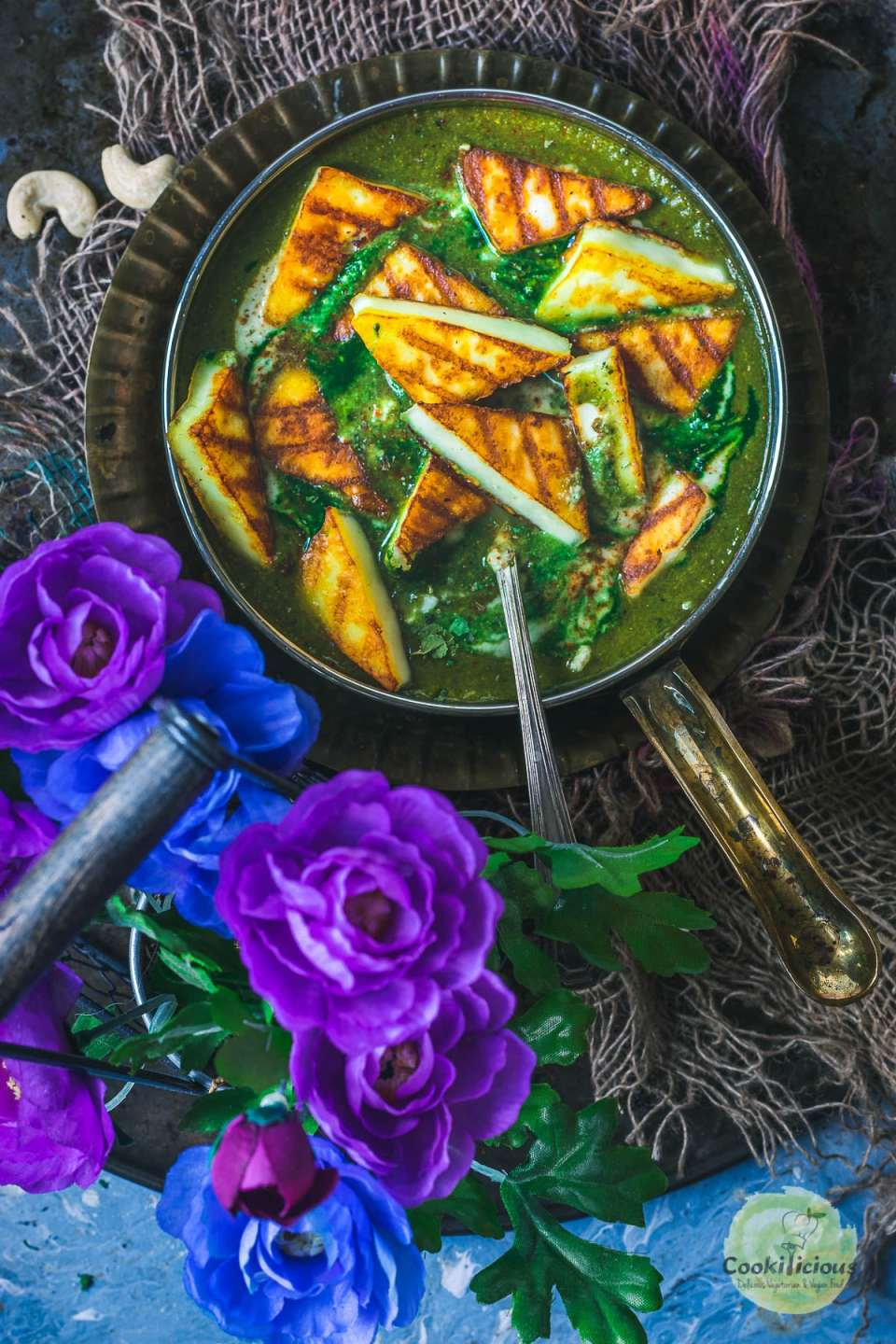 Restaurant Style Palak Paneer served in a bowl with flowers on the side