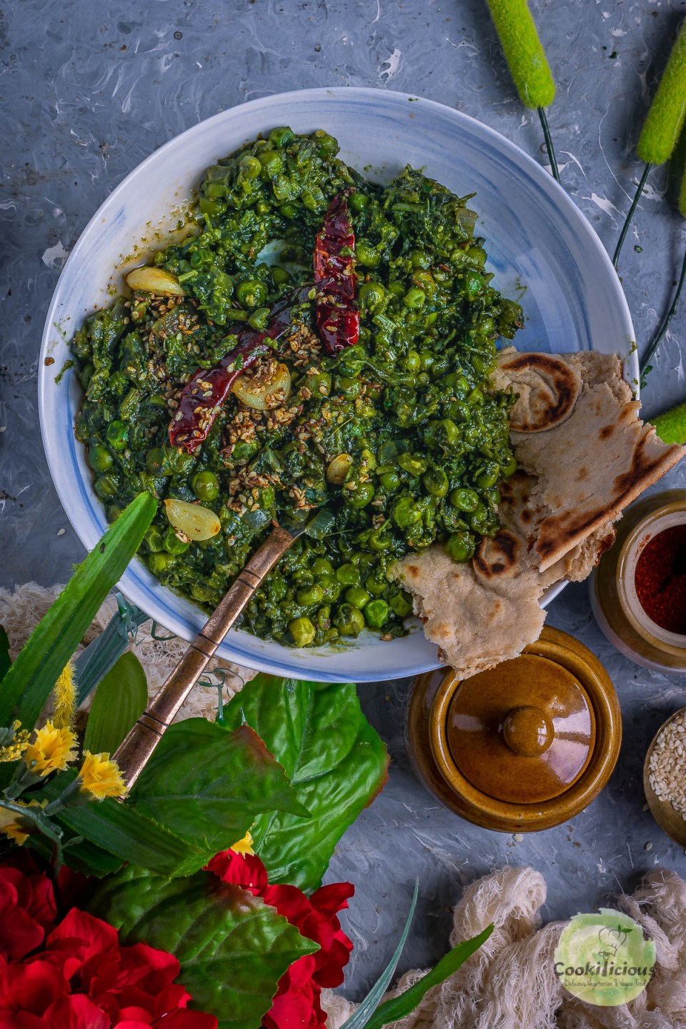 a bowl of Garlicky Peas Spinach Fenugreek Curry with a spoon in it