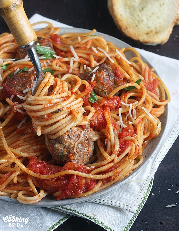forkful of pasta and a meatball on the end of a fork