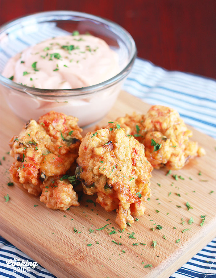 three crawfish beignets on a wooden board with sauce in the background