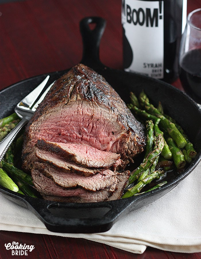 sliced roast beef on surrounded by roasted asparagus in a cast iron pan.