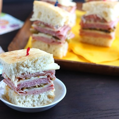 Bite-sized mini muffuletta sandwiches are loaded with sliced meat, cheese, and salty olive salad. These appetizers are loaded with a taste of New Orleans.