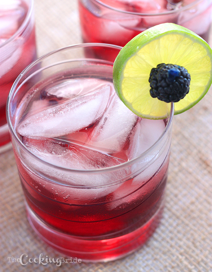 blackberry limeade cocktail in a glass with ice garnished with fresh blackberry and lime slice