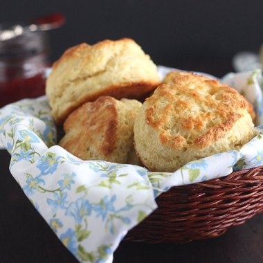 buttermilk biscuits in a basket lined with a floral napkin
