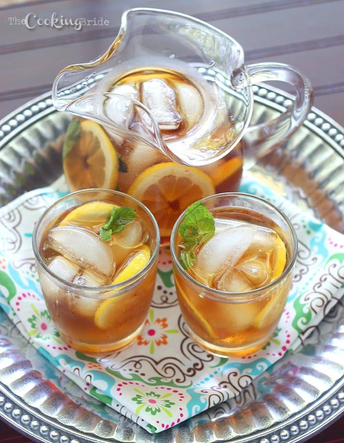 a glass pitcher of sweet tea with lemon and two serving glasses on a pewter tray with a multicolored napkin