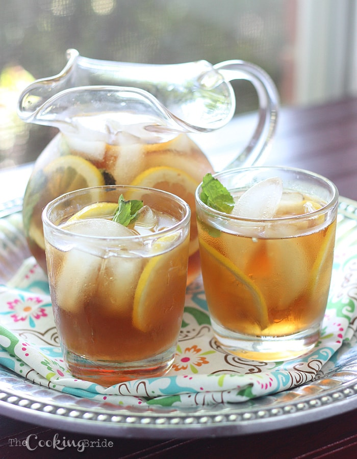 pitcher of sweet tea and two glasses on a pewter serving tray infront of a window