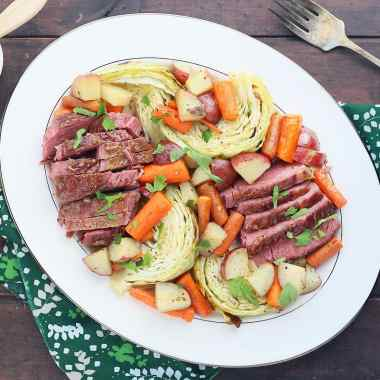 overhead shot of side view of sliced bourbon glazed corned beef and roasted vegetables on a white platter with a green napkin, tarnished silver meat fork, glass of beer and small dish of glaze to the side
