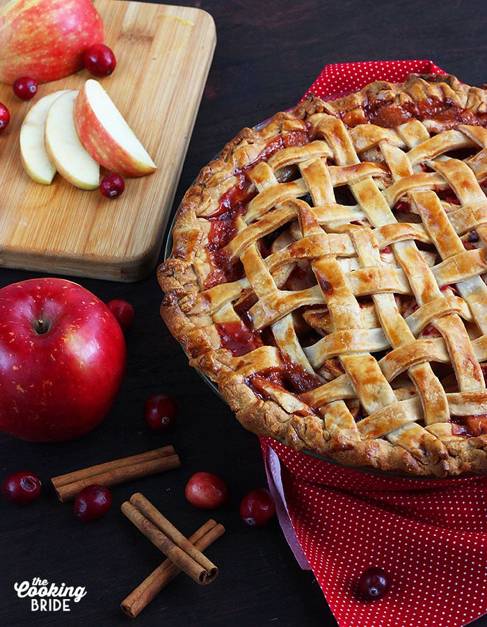 baked cranberry apple pie on a red napkin surrounded by sliced apples, cranberries and cinnamon sticks