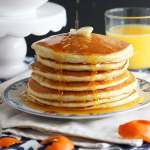 Serve these pillowy soft homemade buttermilk pancakes from scratch drizzled with homemade orange syrup for breakfast. They will melt in your mouth!