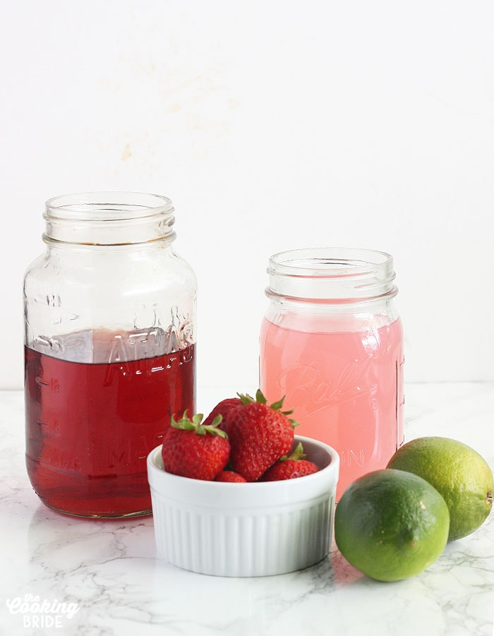 lemonade ingredients including cherry vodka and pink lemonade in a mason jar, fresh limes and fresh strawberries