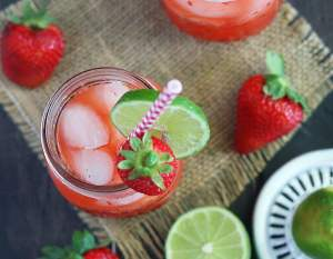 overhead shot of two glasses of vodka lemonade on a wooden background with strawberries and limes surrounding the glasses