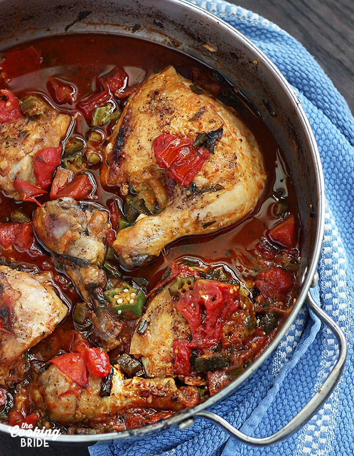 roasted chicken thighs in a skillet with okra and tomatoes