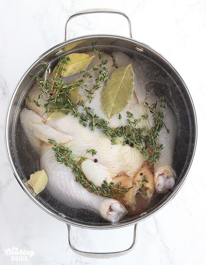 Brining Basics - whole chicken soaking in salt water in a metal stock pot