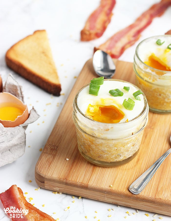 side shot of two egg jars with runny yolks surrounded by bacon , toast and eggs.