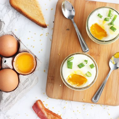 overhead shot of two egg jars with runny yolks surrounded by bacon , toast and eggs.