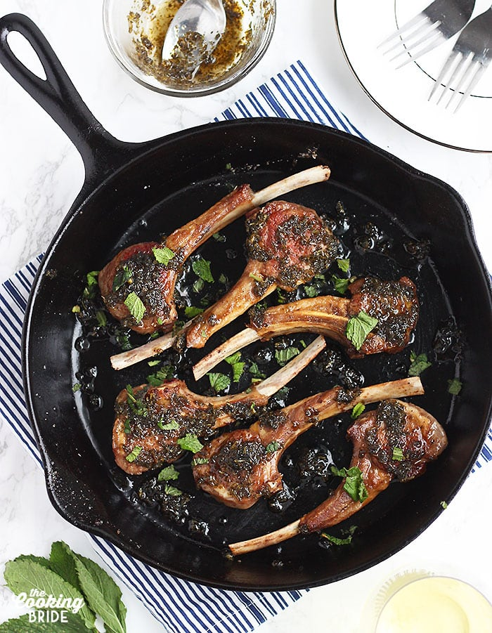 overhead shot of six lamb chops in a cast iron skillet