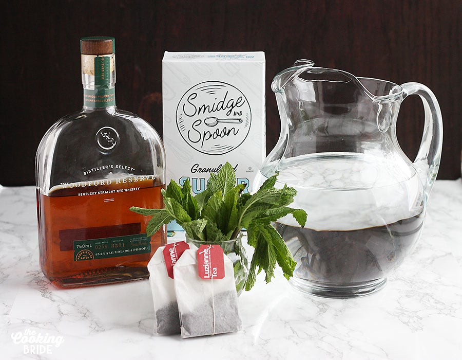 ingredients for a sweet tea mint julep including tea bags, sugar, bourbon and water