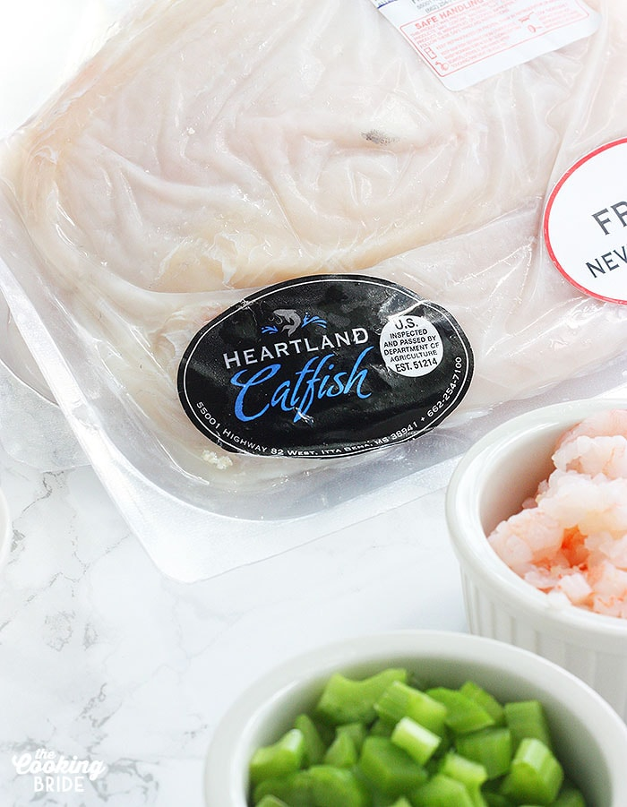 package of Heartland Catfish with label on a white counter surrounded by recipe ingredients