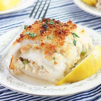 stuffed catfish fillet on a white plate with a blue and white striped napkin underneath