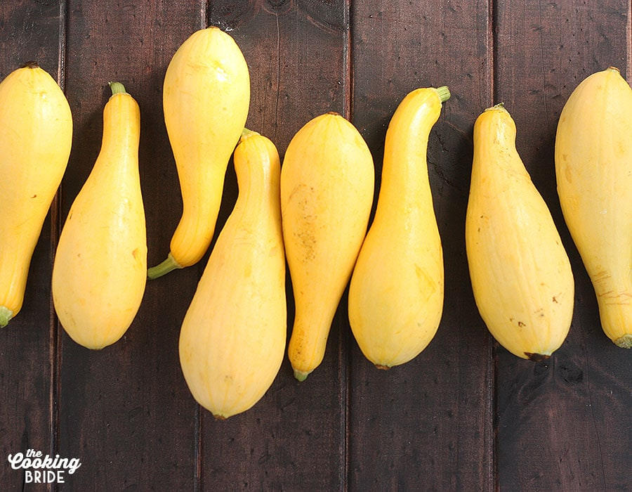 yellow squash lined up horizontally on a wooden table