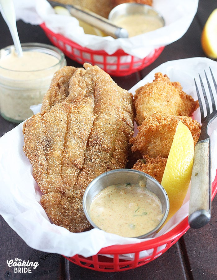 fried catfish fillet laying in a red basket with hushpuppies, remoulade sauce and lemon wedge