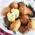 looking down on a bucket of hush puppies on a wooden table with a red napkin