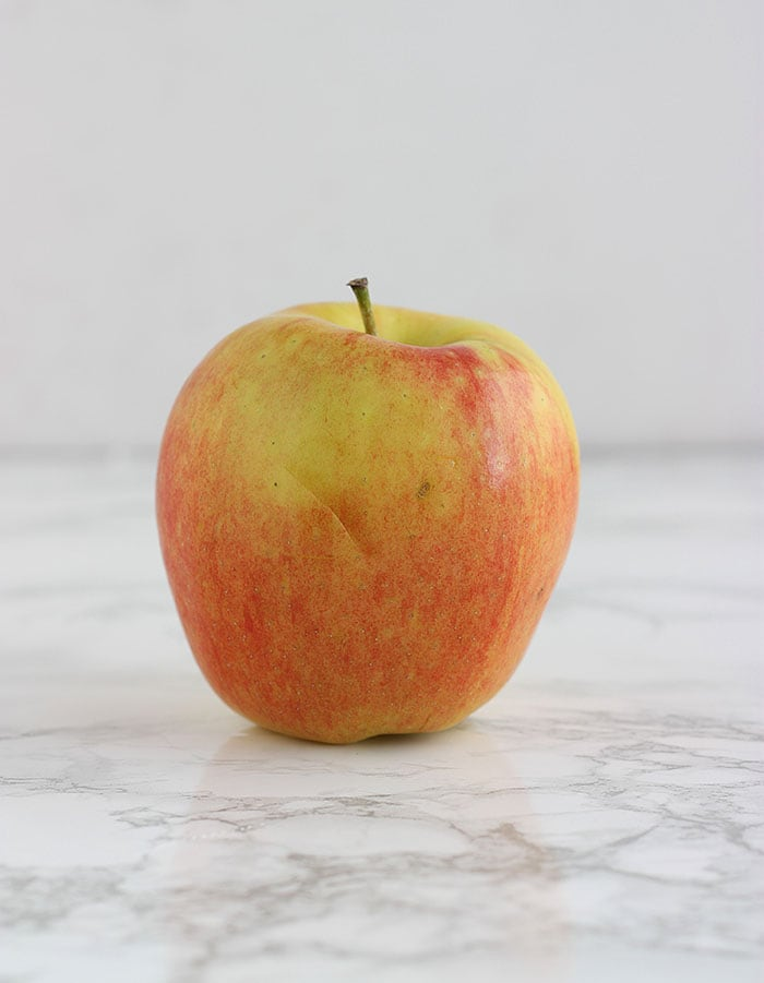 yellow and pink ambrosia apple on a white background