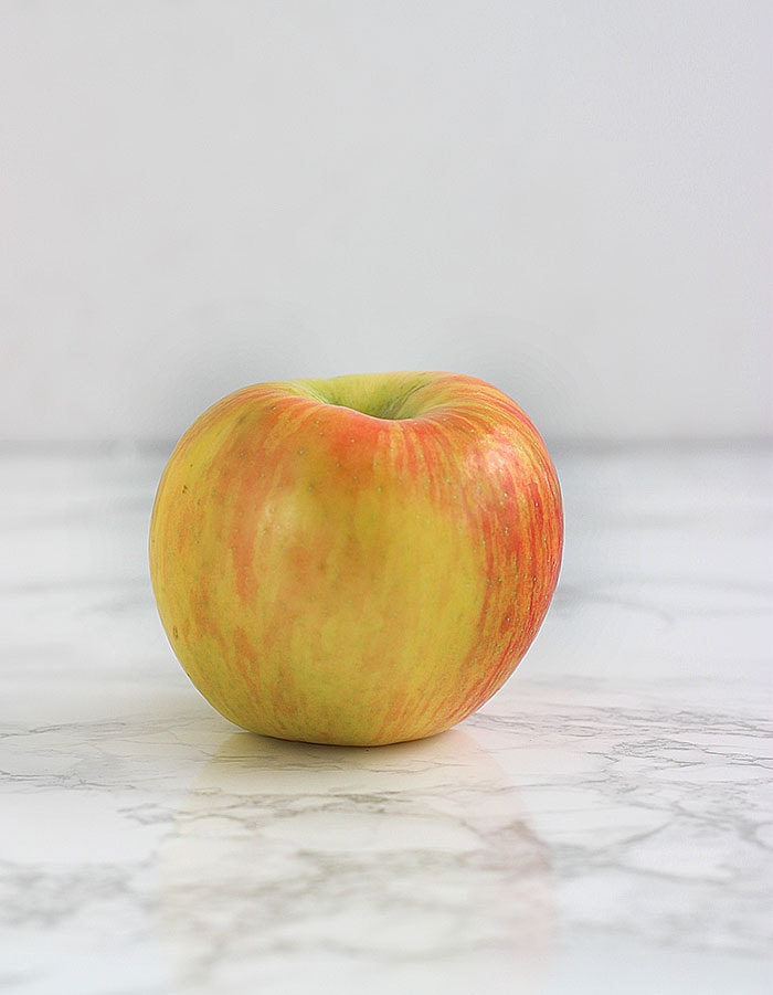 yellow and pink honeycrisp apple on a white background