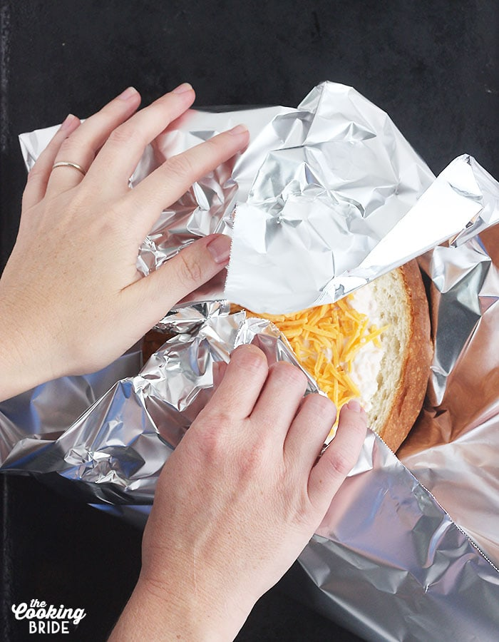 pair of hands wrapping the dip in aluminum foil