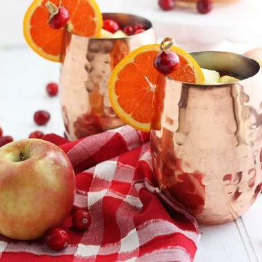 two copper mule cups of spiced apple cider against a red plaid napkin