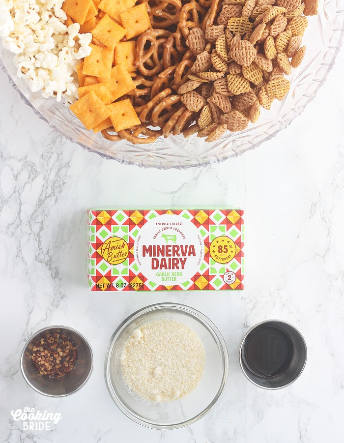 seasoned snack mix ingredients, including crackers, pretzels, cereal, popcorn, garlic herb butter, red pepper flakes, Parmesan cheese and Worchestershire