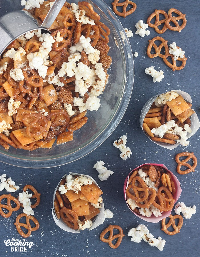 overhead shot of a glass bowl of snack mix and three individual cup of snack mix on a blue background