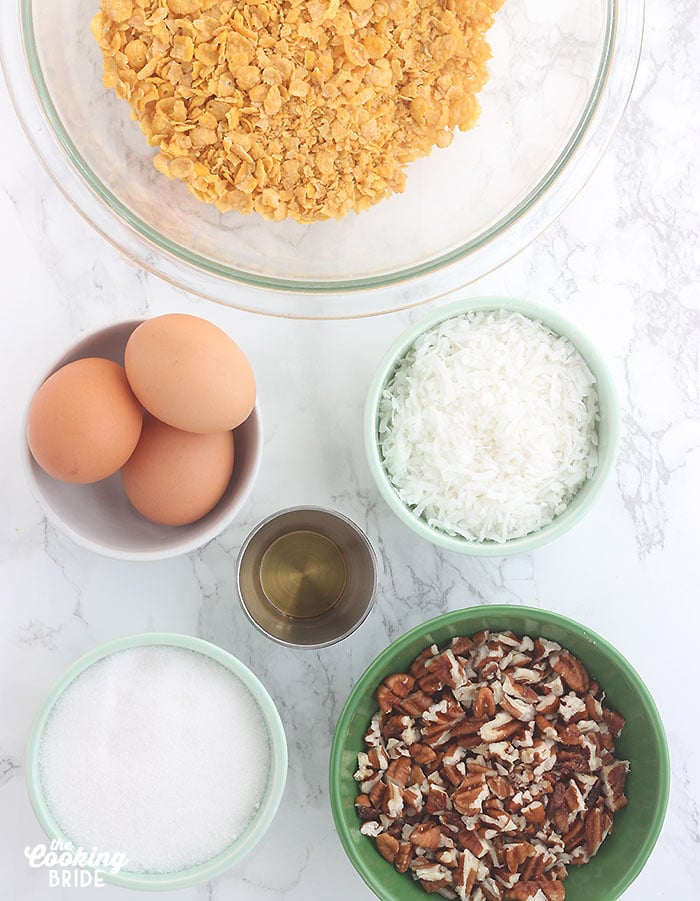 ingredients for cornflake cookies including cornflakes, eggs, coconut, vanilla, sugar and chopped pecans