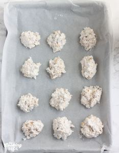 unbaked coconut cookies on a baking sheet lined with parchment paper