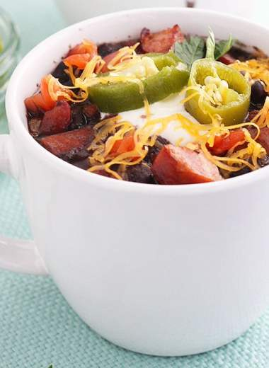 two white mugs full of black bean soup garnished with sour cream, cheese and jalapenos