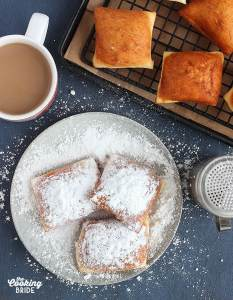 beignets on a grey plate covered in powdered sugar with a mug of cafe au lait on the side