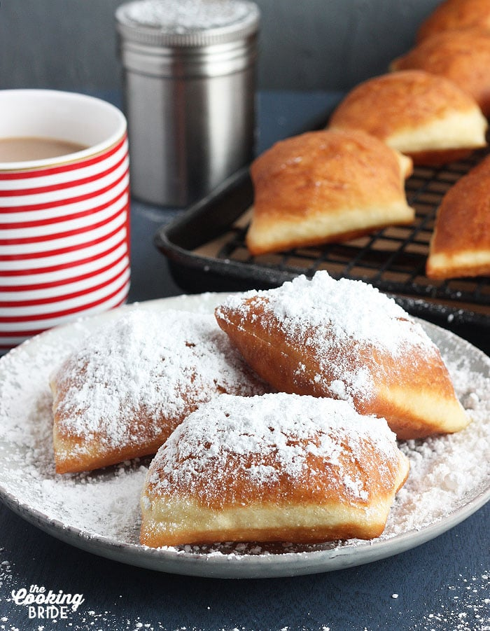 three beignets on a grey plate with powdered sugar with cafe au lait in the background