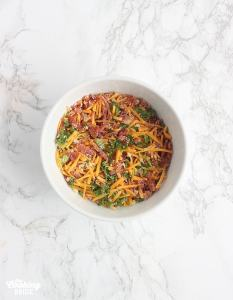 bacon cheddar topping for the eggs on a small white bowl.