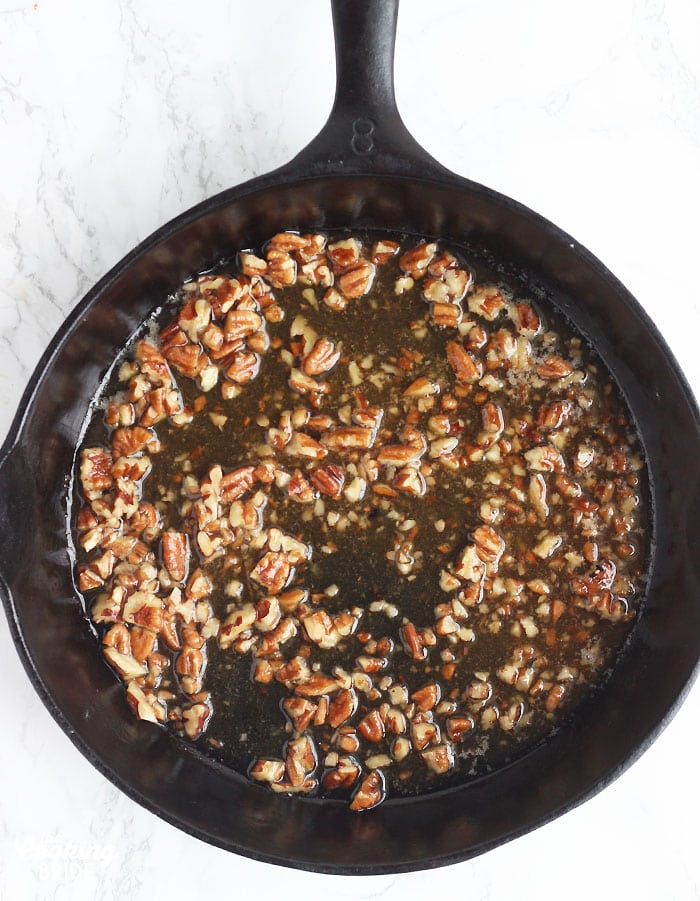 praline topping spread out over the bottom of a cast iron skillet