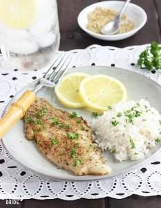 lemon pepper catfish fillet with rice an lemon slices on a gray plate
