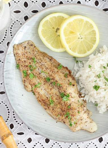 lemon pepper catfish fillet with rice an lemon slices on a gray plate