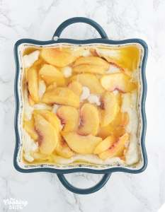 sliced peaches resting on top of the crust batter in a baking dish before baking