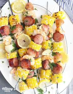 shrimp kabobs with sausage, corn and potatoes threaded on metal skewers on a white platter with a blue and white striped napkin underneath