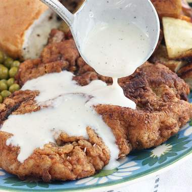 drizzling cream gravy over a piece of country fried steak