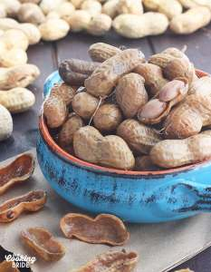 blue bowl of boiled peanuts surrounded by green peanuts in the background