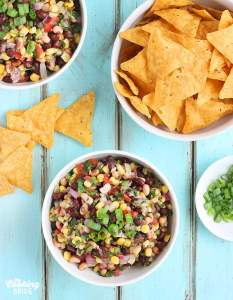 Two while bowls of Texas Caviar on a blue background with a white bowl of tortilla chips and green onions on the side