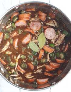 chicken and sausage gumbo in a steel pot with two bay leaves laying on top